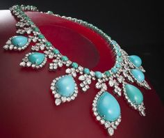 A turquoise and diamond necklace and earclips, circa 1960 designed as a line of round cabochon turquoise accentuated by round brilliant-cut diamond cluster spacers and suspending a graduated fringe of pear-shaped cabochon turquoise, pear and round brilliant-cut diamonds