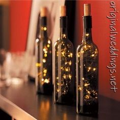 Wine bottle filled with lighting as wedding reception decor using recycled items.  Search for ideas and goods at Estate ReSale  ReDesign in Bonita Springs, FL