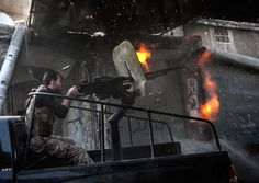 A rebel fighter fires a gun toward a building occupied by Syrian troops in the Jedida district of Aleppo on November 4, 2012. (Narciso Contreras/Associated Press) # - Boston.com