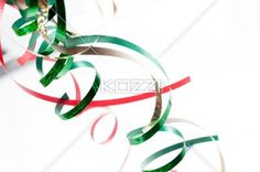 red and green rolled streamers over white background. - Close-up shot of shiny red and green rolled up streamers over white background.