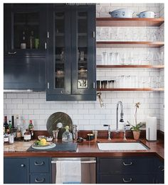 Kitchen natural wood shelves white subway tile dark grey painted cabinets