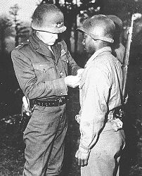 "Lt. Gen. George S. Patton pins the Silver Star on Private Ernest A. Jenkins of New York City for his conspicuous gallantry in the liberation of Chateaudun, France..."", 10/13/1944"