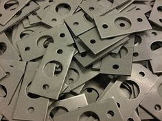 CNC punched Zintec coated mild steel fixing plates waiting to have an M10 bush inserted.