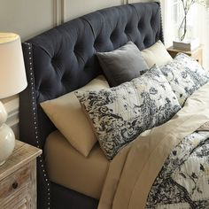 deeply tufted headboard, dotted with shimmering nailhead trim