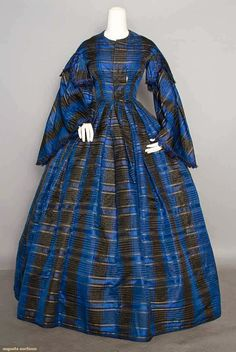 "SILK PLAID AFTERNOON DRESS, 1850-1860  1-piece, sapphire blue & black plaid w/ narrow ivory stripes, capped bell sleeves, knife-pleated skirt, brown glazed cotton lining, B 32"", W 24"", L 57"", (1.5"" tear in front bust dart, silk wear at waistband, silk splits near hem, lining damaged)."