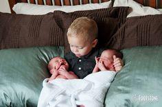 big brother holding newborn twin brothers
