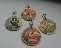 Custom etched brass, copper, nickel dog tag. Bone, Fleur de lis, paw prints.