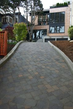 Pretty stone paved drive way. Pretty modern house. Love the dark trim, brick and concrete. That large tree in front makes a difference too.
