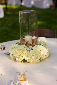 candle centerpiece with hydrangea, scabiosa, ranunculus, and cork