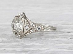 Antique Edwardian engagement ring made in platinum and centered with an EGL certified 1.05 carat old European cut diamond with G-H color and SI2 clarity. Circa 1925 This ring features an unusual diamond shaped mounting that speaks to the Art Deco era's focus on geometric patterns and graphic shapes. Diamond and gold mining has caused devastation in areas such as Africa, wreaking havoc on delicate ecosystems and communities. Choosing to go vintage, you are eliminating the need for more…