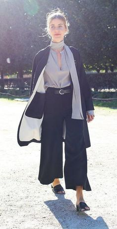 Sophie Buhai in a silk v-neck blouse, black wide-leg pants and black slides with a light jacket