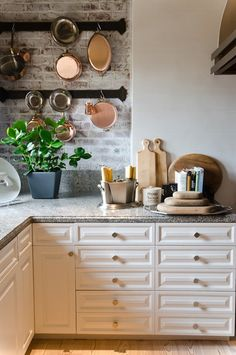 Traditional kitchen by Alex Amend Photography. White cabinets, brick backsplash, hanging copper pots, rustic, corian or quartz.