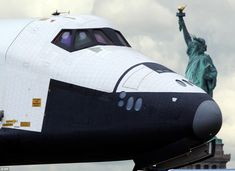 The space shuttle Enterprise moves past the Statue of Liberty as it floats on a barge to the flight deck of the USS Intrepid