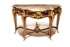 A French ormolu-mounted kingwood console table by François Linke, Circa 1900. Surmounted by a shaped brèche violette marble top, centred to the front by a scallop shell, flanked to each side by scrolling foliage, on four cabriole legs, each headed by a female caryatid, the front right signed Linke, joined by an 'X'-shaped stretcher, centred by a Watteauesque man holding a mandolin, seated on a pierced foliate base, on foliate sabots