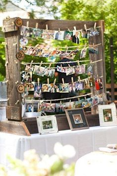 Photo display at garden party or a wedding. Made to look rustic with old boards and clothesline style, hanging the pictures with clothespins.