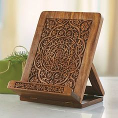 Wooden iPad Stand -Hand-carved from sustainable shesham wood by master artisans in India, our stand displays the beauty of floral mandala woodwork while displaying recipes - either on your iPad or in a cookbook. We collaborated with a non- profit fair-trade organization that helps impoverished, often physically handicapped carvers promote their masterful products.