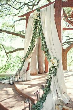 Beautiful combination of rustic with grace and elegance. Love the lanterns and fabric with the greenery garland.
