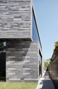 Like a naturally occurring trilithon found in rock formations, the Canterbury Road Residence by b.e architecture in Melbourne, Australia is made up of three simple structures, clad in rough lavastone stacked to form a contemplative passageway. Modern Architecture Design, Facade Design, Facade Architecture, Modern House Design, Exterior Design, Residential Architecture, Stone Cladding Exterior, House Cladding, Stone Facade