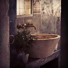 Rustic bathroom sink with brass faucet and stone bowl.