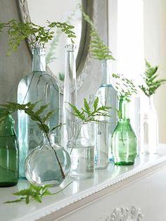 Garrafas e vidros sobre o aparador com ramos de folhas