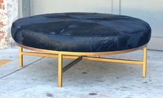 Chic Oversized Gilt Metal and Black Calfskin Ottoman | From a unique collection of antique and modern ottomans and poufs at http://www.1stdibs.com/furniture/seating/ottomans-poufs/