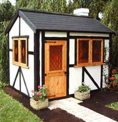 Tudor Cottage ~ One of our most popular playhouses, the Tudor Cottage is available prepainted externally with white panels and black bracing. Internal stain is light oak. Mock leaded and coloured glazing, felt roof tiles and chimney.