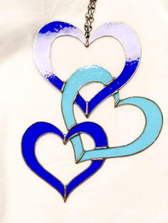 This beautiful intertwined hearts suncatcher is the perfect way to say I love you or would be a wonderful addition to any heart collection! This cute piece of art is made with blue and purple water glass and it reflects the suns rays in a mesmerizing way. The intertwined hearts