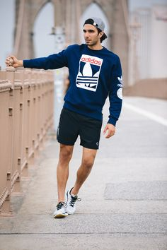 Navy sweatshirt w/ white retro Adidas logo (orange lettering), black running shorts & black-laced white running shoes, grey bill-back cap