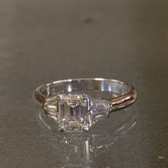 18K white gold emerald cut diamond engagement ring with custom cut double baguette diamond shoulders.