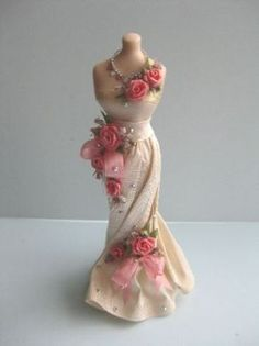 Ladies gown on  quality ceramic mannequin, White silk off the shoulder design with slim skirt trimmed with pink ribbon and pink rose cascade, and pretty diamante necklace.