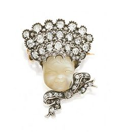 CARVED MOONSTONE AND DIAMOND BROOCH, TIFFANY & CO., CIRCA 1890  Estimate: 4,000 - 6,000 USD   LOT SOLD. 13,200 USD  (Hammer Price with Buyer's Premium)  Designed as a baby with carved moonstone face, wearing a bonnet and bow set with old-mine and rose-cut diamonds, mounted in gold and silver, signed Tiffany & Co.