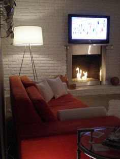 Modern Fireplace, white-painted brick wall, television, gray walls, tan carpet