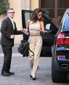 Selena Gomez wearing White Cropped Top, Beige Wide Leg Pants, Black Leather Satchel Bag, and Black Suede Heels
