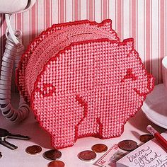 """Penny-Wise Pig Bank Plastic Canvas ePattern - A telling smile suggests that this penny-wise pig knows the secret to saving for a trip to the market. Ample in size, the cute bank has an easy-open bottom for withdrawing your investments. The project is stitched on 7 mesh plastic canvas using worsted weight yarn. Number of Designs: 1 bank Approximate Design Size: 6 5/8""""w x 5""""h x 3""""d"""