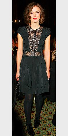 in a lace-bodice Nina Ricci frock worn with black tights and a quilted clutch