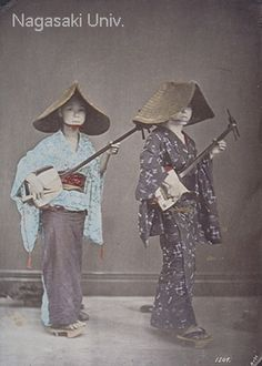"""Although entitled """"Japanese Singers,"""" this staged scene actually shows """"torioi"""" (bird chasing) strolling musicians. Originally part of celebratory ritual, """"torioi"""" eventually turned into a custom called """"Kadozuke-gei."""" The torioi were strolling female musicians wearing distinctive """"amigasa"""" hats and playing the shamisen. They went from door to door playing music and expressing good wishes for a small charge. about 1880's, by Usui Shuzaburo"""