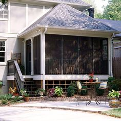Screened porch with peaked roof, landscaping that surrounds the addition and a pretty patio.  Nice.