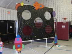 Stomp Rocket into the Milky Way game. We used a black tarp, hula hoops for the holes, and sticky foam stars with cardboard cutouts for decoration.  Kids shot stomp rockets through the holes.  It was the favorite game of our space themed party!