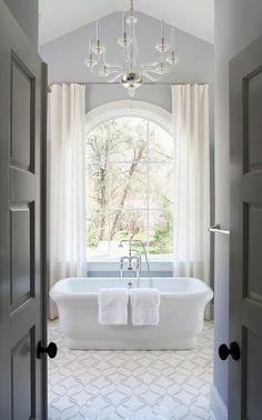 Elegant, traditional bathroom features a Calacatta Tia and honed Thassos Tiles, New Ravenna Sophie Tiles, lead to a freestanding rectangular bathtub paired with a vintage style hand-held tub filler placed below an arch window dressed in white curtains illuminated by a glass chandelier.