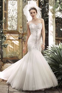 A stunning fit and flare featuring pleated tulle, this dramatic wedding gown is accented with glamorous Swarovski crystals and pearls tracing the sweetheart neckline, trailing the center of the bodice and flaring into a voluminous skirt. Maggie Sottero, Fall 2015