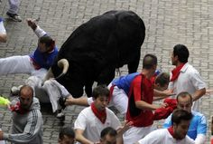 """A runner (partially obscured on L), is gored in the right thigh by the 600kg Victoriano del Rio fighting bull """"Brevito"""" during the third running of the bulls at the San Fermin festival in Pamplona July 9, 2014. This runner was identified by the website sanfermin.com as Bill Hillman, co-author with John Hemingway, of the book """"How to Survive the Running of the Bulls"""". The 32-year-old American, from Chicago, was gored in the thigh, a doctor told Spanish state television. REUTERS/Eloy Alonso"""