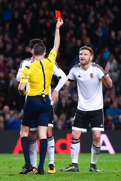 Shkodran Mustafi of Valencia CF is shown a red card by the referee Ignacio Iglesias Villanueva for a challenge on Lionel Messi of FC Barcelona during the Copa del Rey Semi Final first leg match between FC Barcelona and Valencia at Nou Camp on February 3, 2016 in Barcelona
