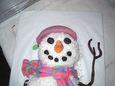 Snowman cake I put together real quick for a family holiday get together. White cake with raspberry filling, lemon cream cheese frosting covered in coconut Homemade fondant decorations, I like the scarf the best!! Homemade chocolate fondant for her arms.