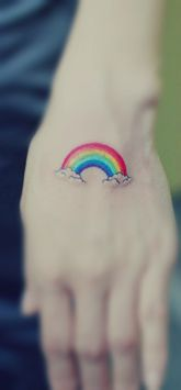 cute rain bow tattoo with two ends on a hand