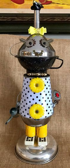 This little gal has just been tending her garden & carries a flower & her watering can. Her cute polka dot frock is actually a metal bucket, her legs are old Kodak canisters & her feet are vintage dominos. Her face is a combo of a metal camp cup, a stainless funnel, her eyes, old keys. I wonder if she knows she has a little blackbird on her head? She stands a stately 16 tall while her base is 6