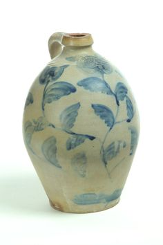 "OHIO STONEWARE JUG.   Mid 19th century. Impressed ""T. Reed, 2"". Ovoid with applied handle and covered in brushed cobalt tulips. 14.5""h. T. Reed worked in Mogadore, Ohio."