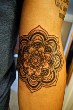 Gorgeous, detailed mandala flower forearm tattoo.