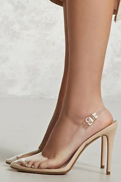 A pair of clear shoes featuring an ankle strap with a buckle closure, a pointed toe, and stiletto heels.
