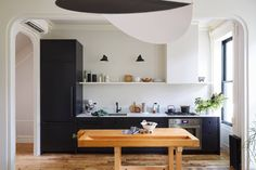 Architect Jess Thomas's compact and streamlined kitchen in her Brooklyn townhouse has black stained cabinets with cutout pulls and open and closed storage.