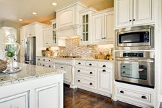 traditional White kitchen cabinets, tile backsplash, wood floors, granite countertops